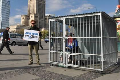 Новости - Сторонники Greenpeace установили в Варшаве клетку Фото: страница польского Greenpeace в Facebook