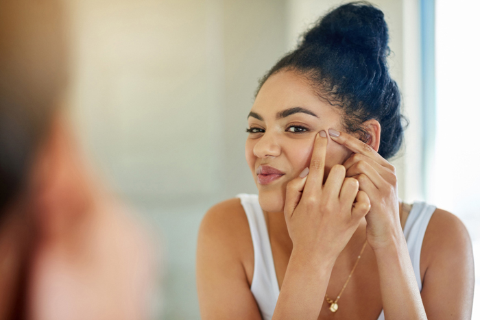 Shot of a young woman squeezing a pimple in front of the bathroom mirror