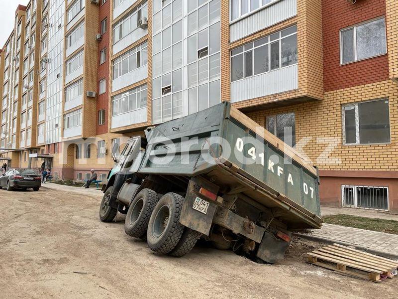 КамАЗ наполовину провалился в Уральске (фото) КамАЗ до кузова провалился под землю в Уральске (фото)